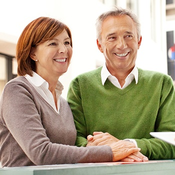 Smiling older man and woman at reception desk