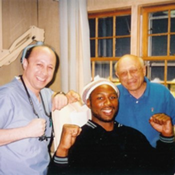 Dr. DeMartino and his father posing with Lennox Lewis