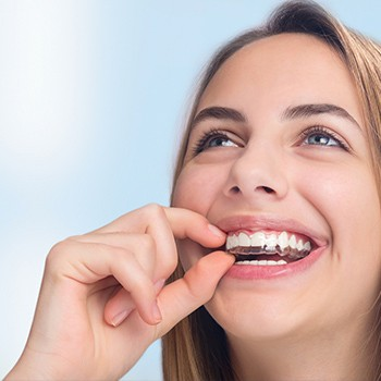 Young woman placing Invisalign tray