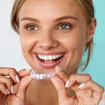 Woman putting her Invisalign tray in place