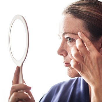Woman looking at fine lines in mirror