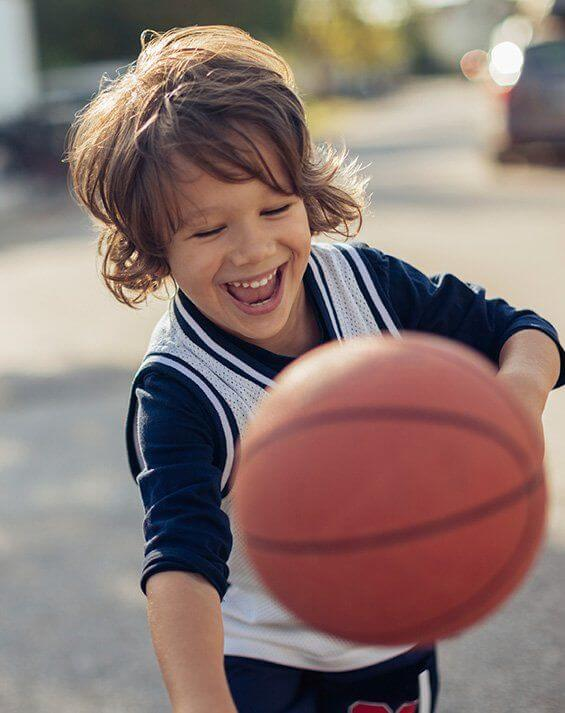 Laughing child playing basketball