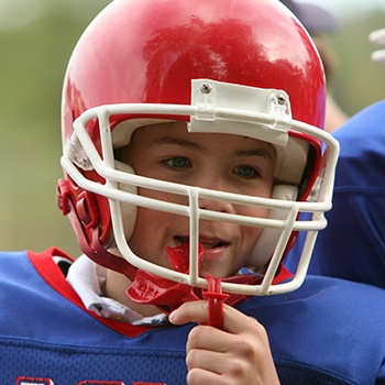 Teen boy placing red mouthguard