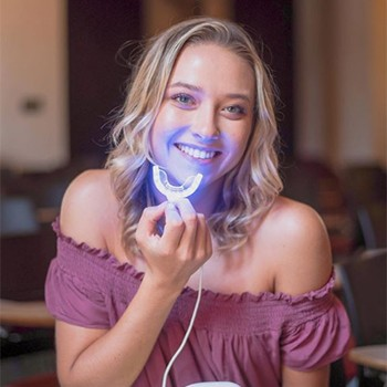Young woman holding Glo teeth whitneing appliance
