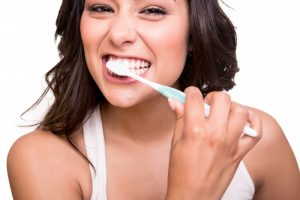 A woman brushing her teeth.