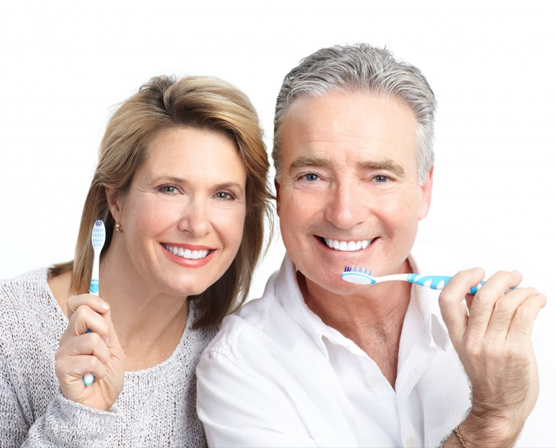 An older couple holding toothbrushes and smiling.