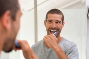 Man looking in the mirror while brushing his teeth