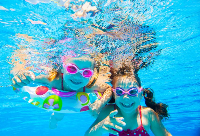 two girls smiling underwater in a swimming pool